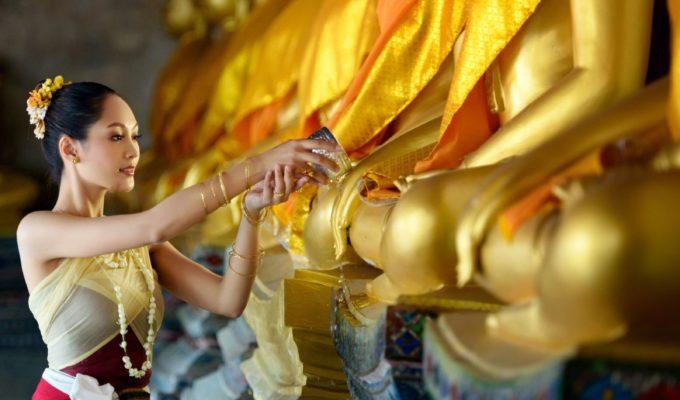 Frau bewässert Buddha am Neujahrsfest, Laos